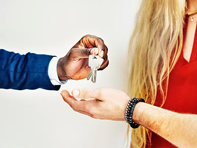 real estate agent handing couple keys to their new home